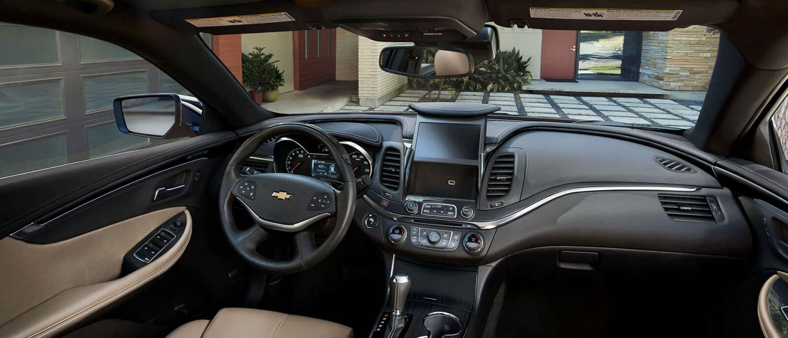 The black and tan interior of the front area of the 2017 Impala is shown with a touchscreen and other high tech and safety features.