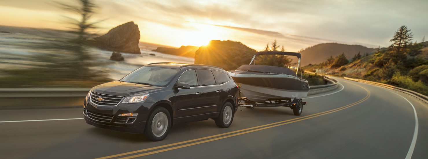 A black 2017 Chevy traverse is towing a boat while the sun it setting near Cincinnati, OH.