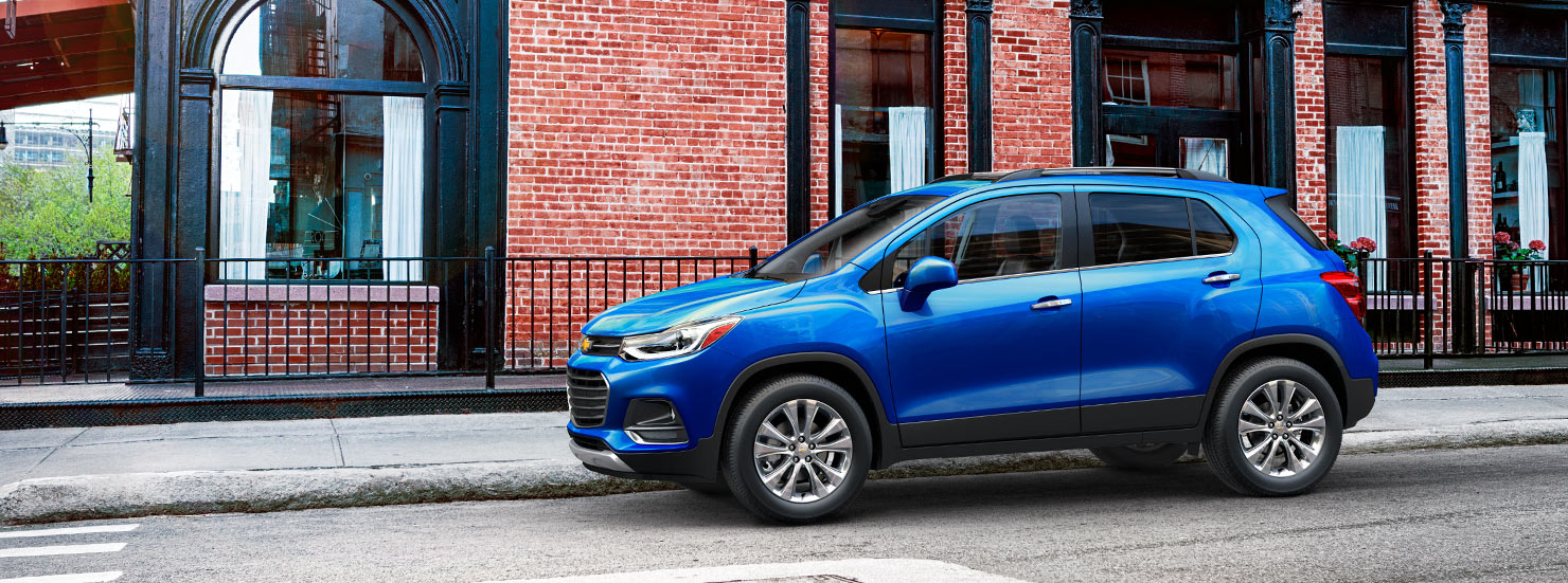 A blue 2017 Trax is parked in front of a brick building.