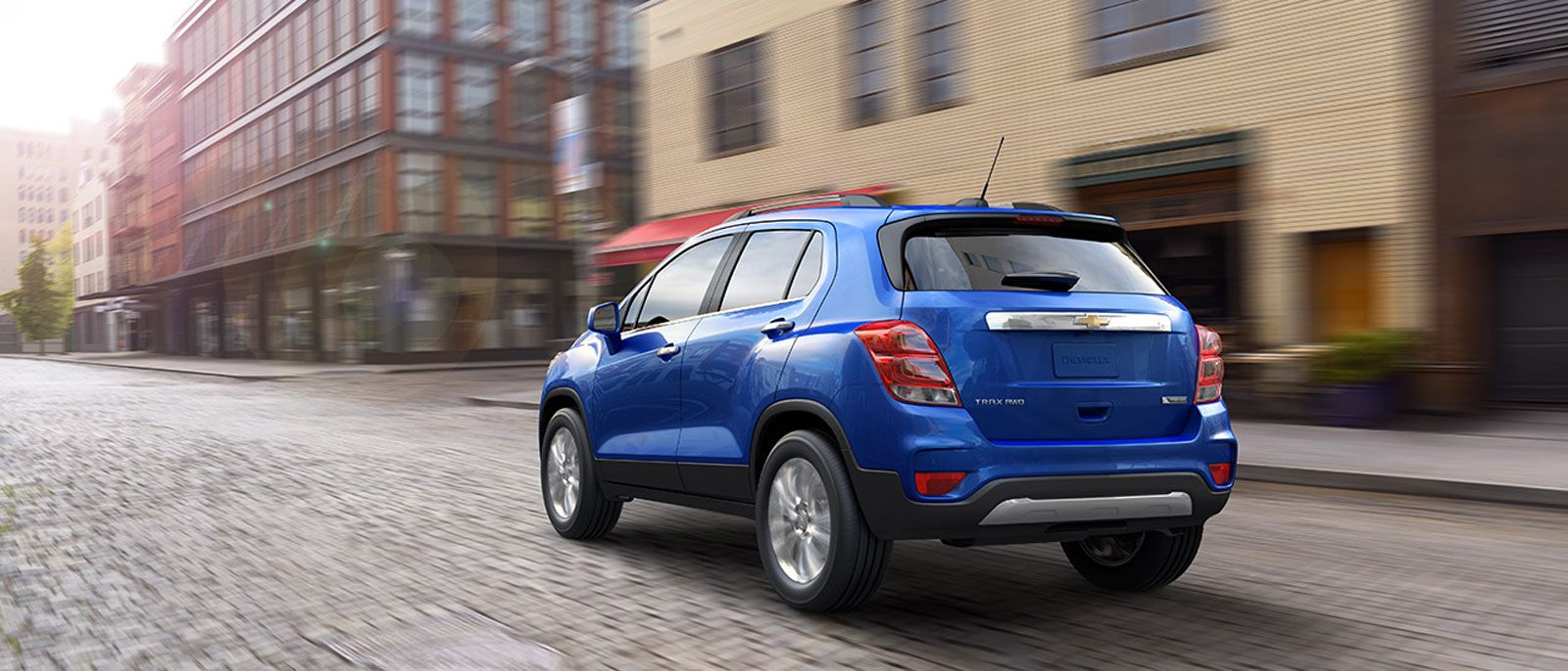A blue 2017 Chevy Trax, which wins when comparing the 2017 Chevy Trax vs 2017 Kia Soul, is driving down a city street near Cincinnati, OH.