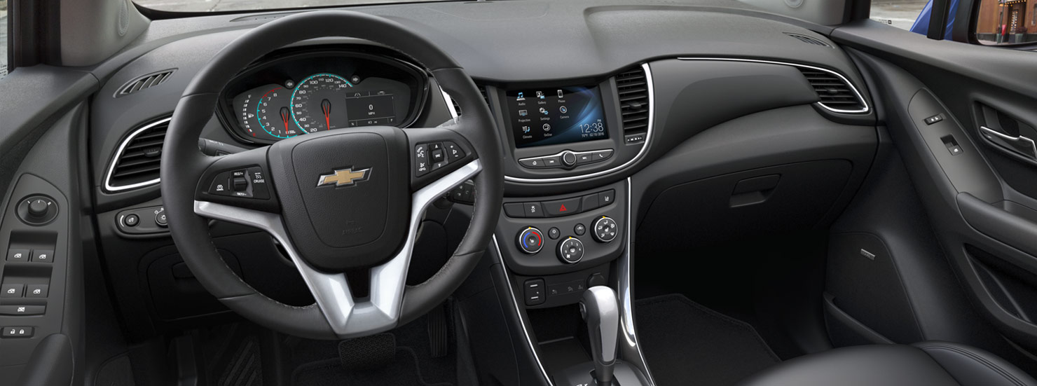 The black interior of the 2017 Chevy Trax is shown with a touchscreen on the front dashboard.