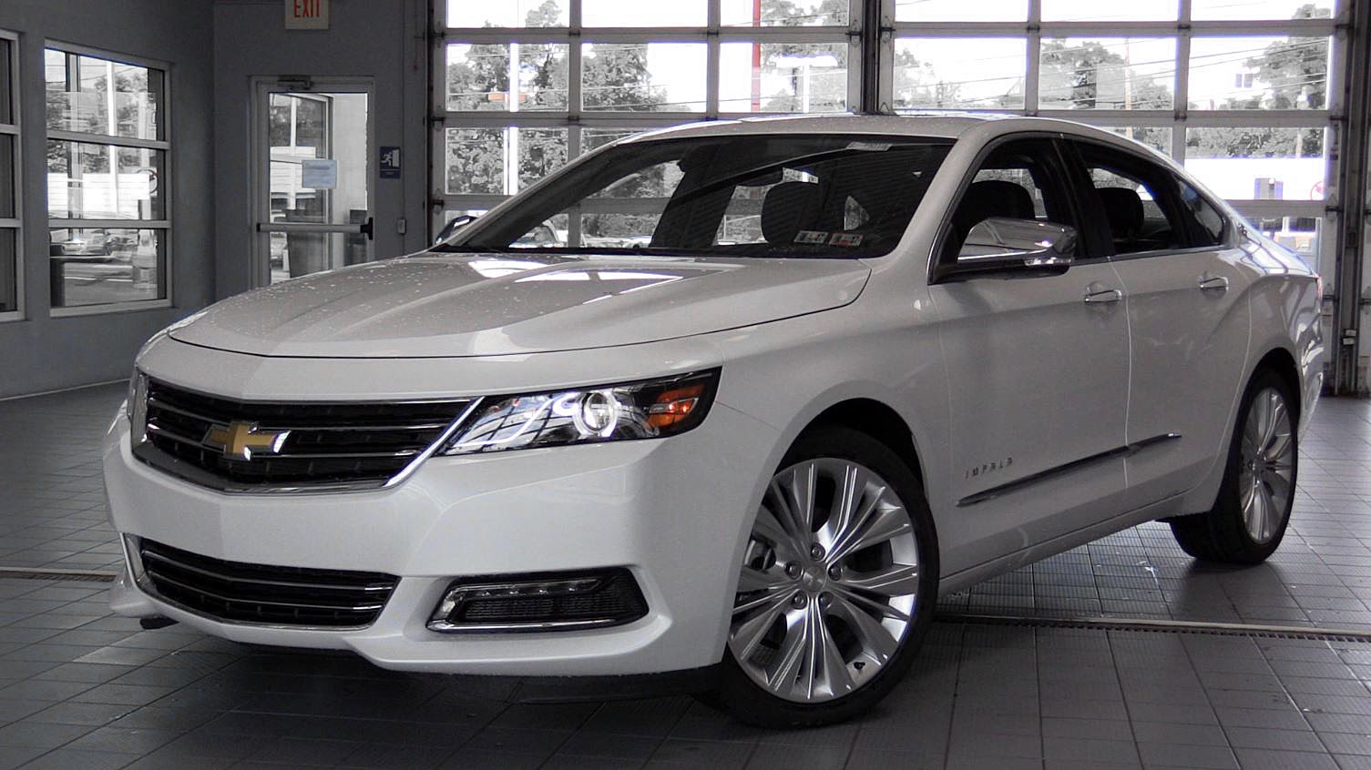 A white 2017 Chevy Impala is parked inside a dealership.