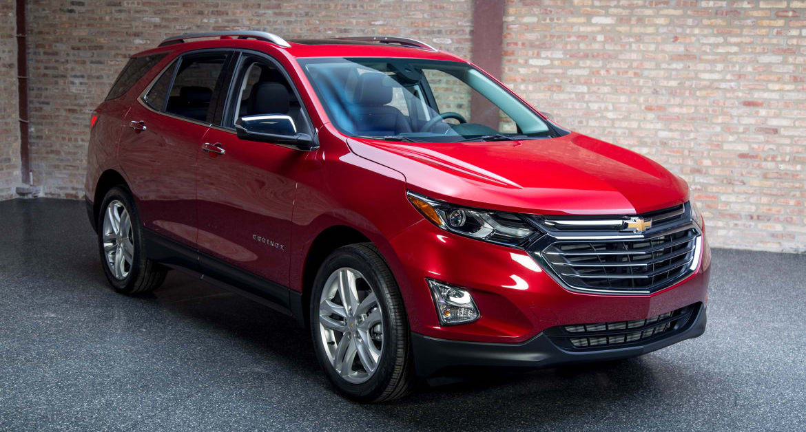 A red 2018 Equinox is parked in front of a brick wall during the day.