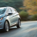 A silver 2017 Chevy Bolt is driving around a blurred corner outside of Cincinnati, OH.