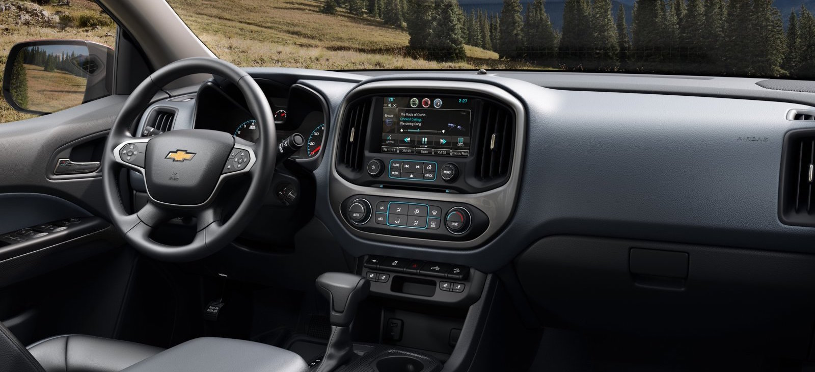 The black and grey interior of a 2016 Chevy Colorado with a touchscreen is shown.