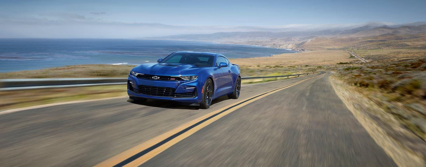 One of the many Chevy lease deals available, a blue 2020 Chevy Camaro SS is driving along the coast.