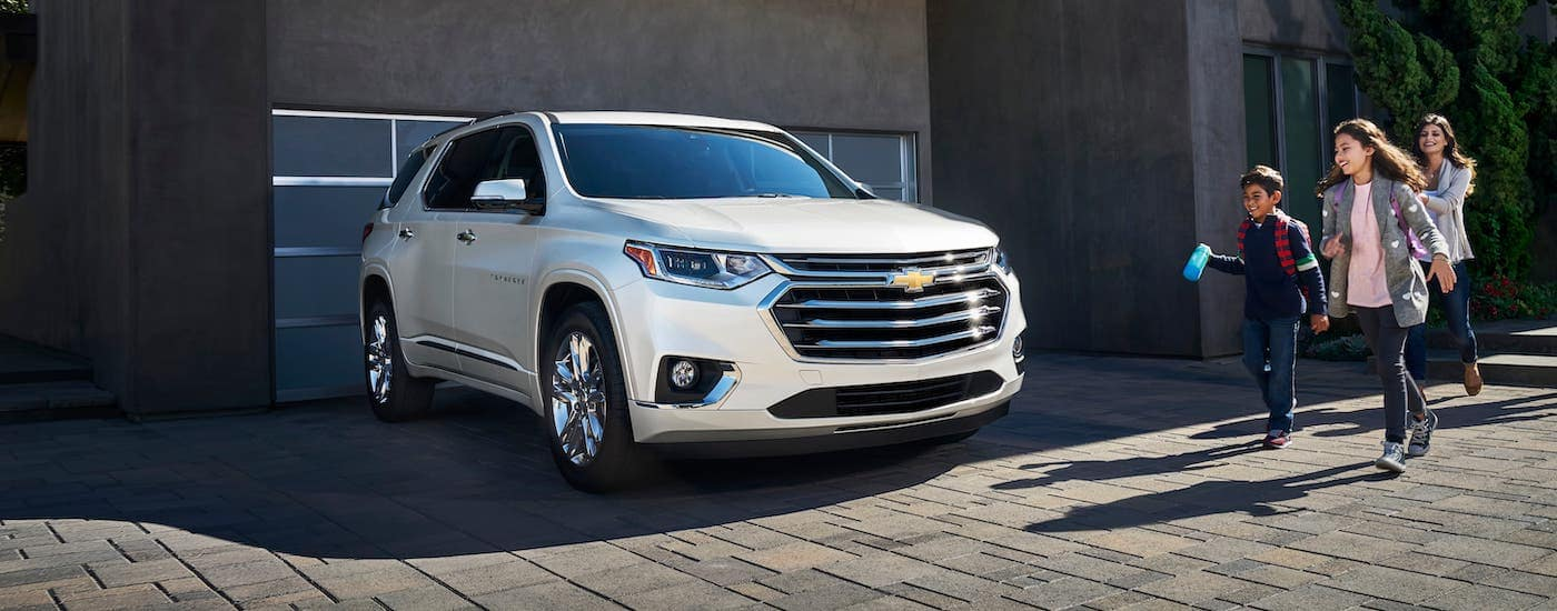 A white 2020 Chevy Traverse is parked in the driveway of a modern home in Cincinnati while a family walks towards it.