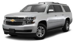 A silver 2017 Chevy Suburban is parked and facing left.