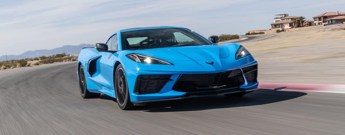 A blue 2020 Chevy Corvette is driving on a race track in a desert.