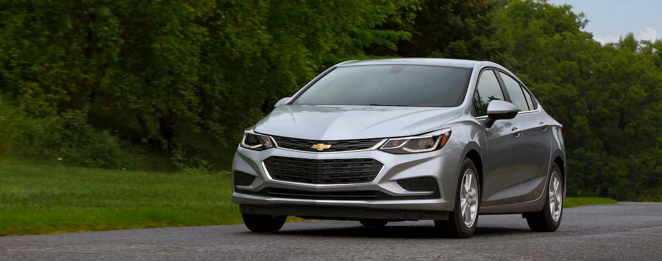 A silver 2017 Chevy Cruze, which wins when comparing the 2017 Chevy Cruze vs 2017 Nissan Sentra, is driving down a road near Cincinnati, OH.