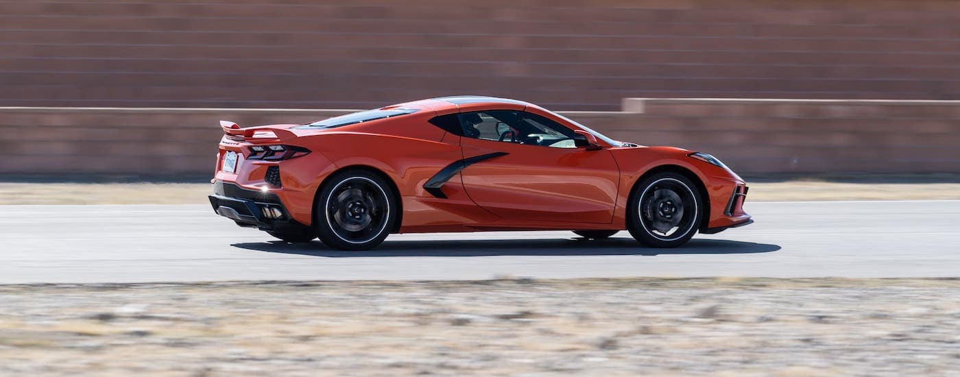 A red 2020 Chevy Corvette Stingray from a Chevy dealership in Cincinnati is racing around a track.