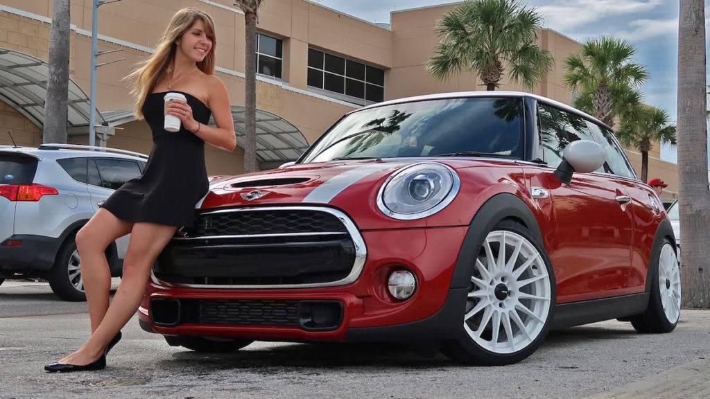 A woman in a black dress holding a coffee leaning against a red Mini Cooper