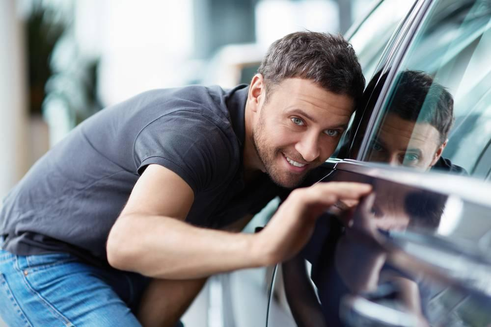 A man inspects a new car with his head close to the window