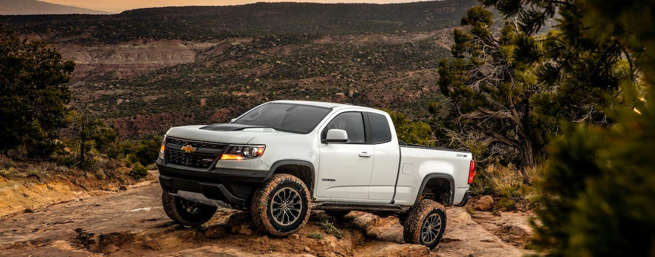 A white 2017 Chevrolet Colorado ZR2, Special Edition, is crawling up a rocky hill.