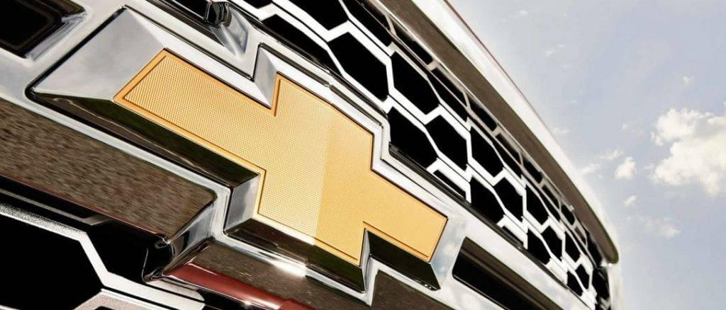 A closeup is shown of the gold Chevrolet bowtie emblem on a 2014 Silverado 1500.