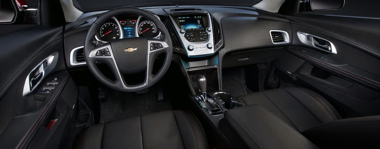 The front black leather interior of a 2017 Chevy Equinox with a touchscreen and other high tech features.