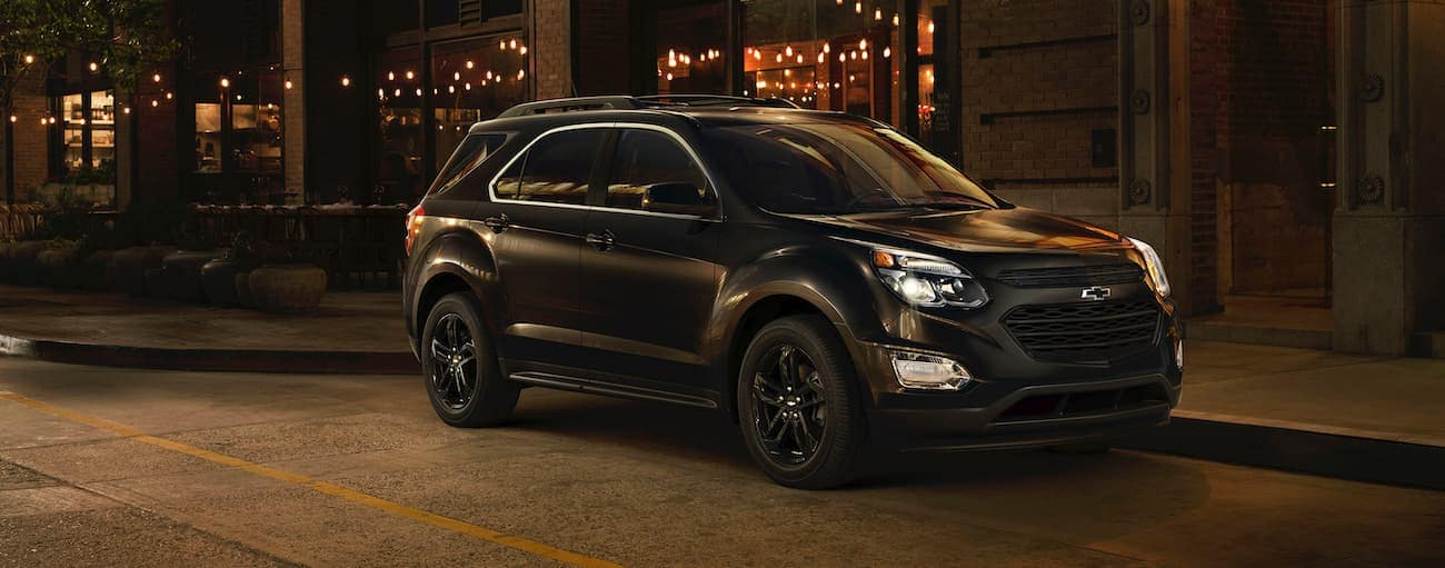 An all-black 2017 Chevy Equinox is parked in front of a building in Cincinnati, OH, at night.