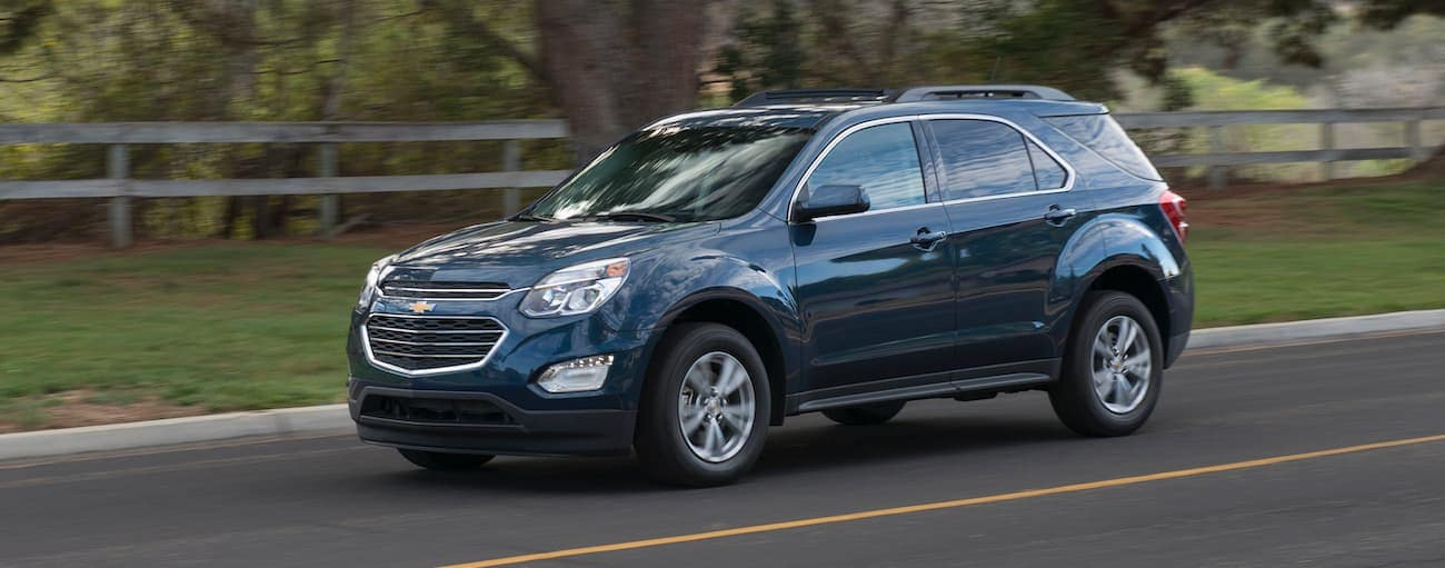A dark blue 2017 Chevy Equinox, which wins when comparing the 2017 Chevy Equinox vs 2017 Honda CR-V, is driving past a fence and trees.