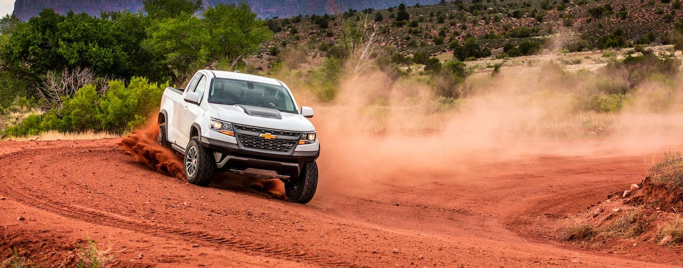 A white 2017 Chevy Colorado ZR2 is kicking up dirt on a desert track, on its way to pick up Chevy accessories.