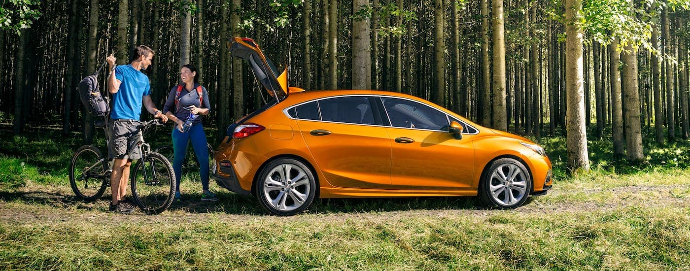 An orange 2018 Chevy Cruze Hatchback has the liftgate open as a couple gets their bikes and other Chevy accessories ready for a woodland ride.