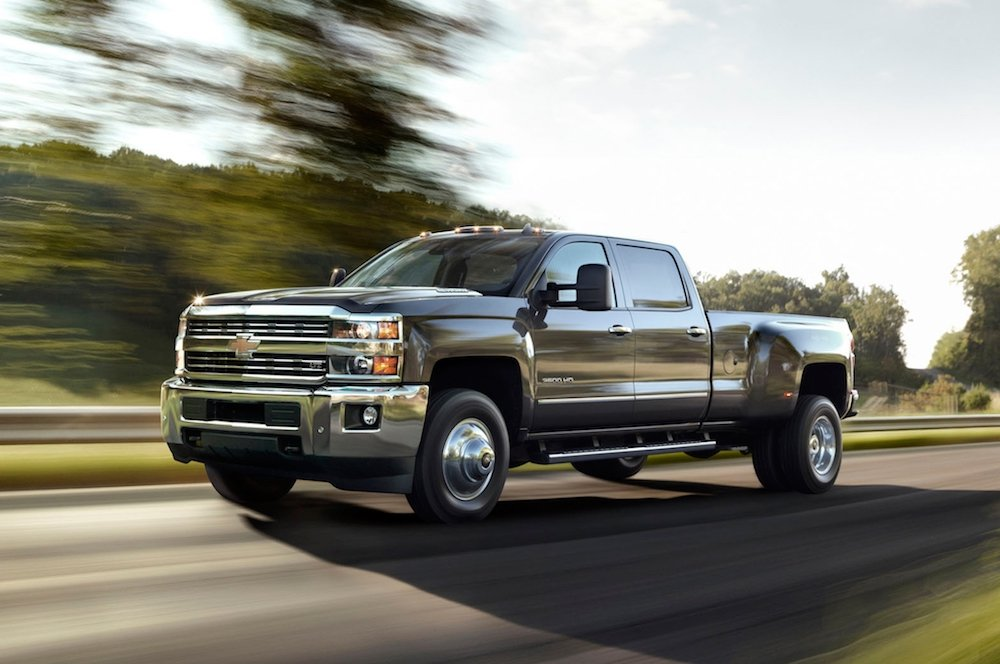 A black 2015 Chevy Silverado 3500HD with dual rear wheels is driving on a rural highway.