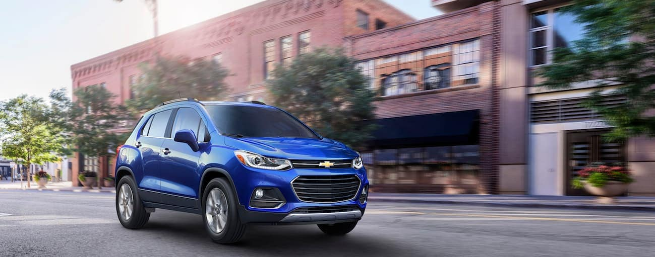 A blue 2017 Chevy Trax, which wins when comparing the 2017 Chevy Trax vs 2017 Mazda CX-3, is driving in a town near Cincinnati, OH.
