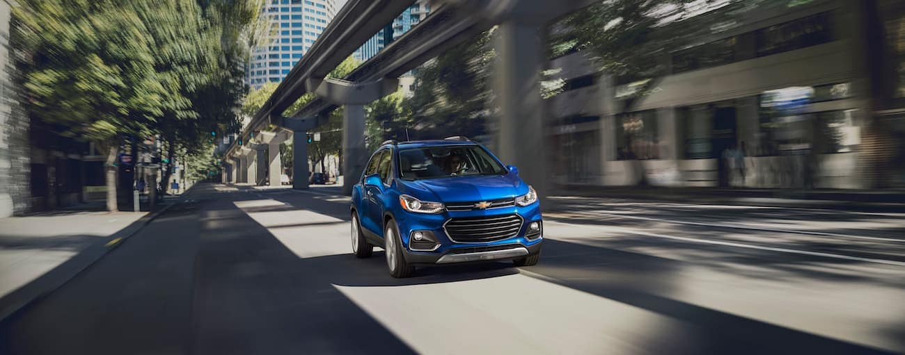 A blue 2018 Chevy Trax is driving through a city with a highway next to the vehicle.