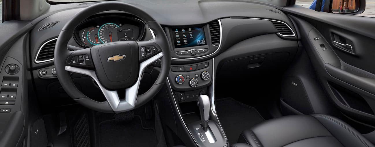 The black and chrome accent interior of the 2017 Chevy Trax is shown with a touchscreen.