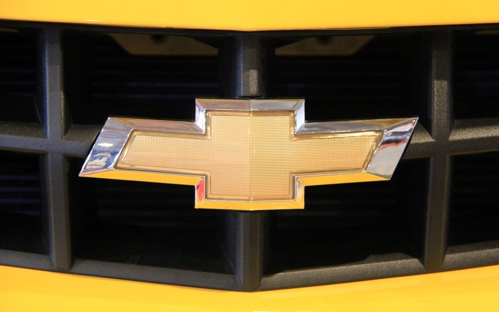 The closeup is shown of a gold Chevy bowtie emblem on a yellow Camaro.