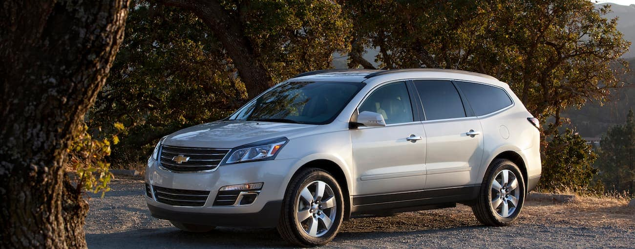 A 2017 Chevy Traverse is parked, which wins when comparing the 2017 Chevy Traverse vs 2017 Honda Pilot, with trees behind it near Cincinnati, OH.