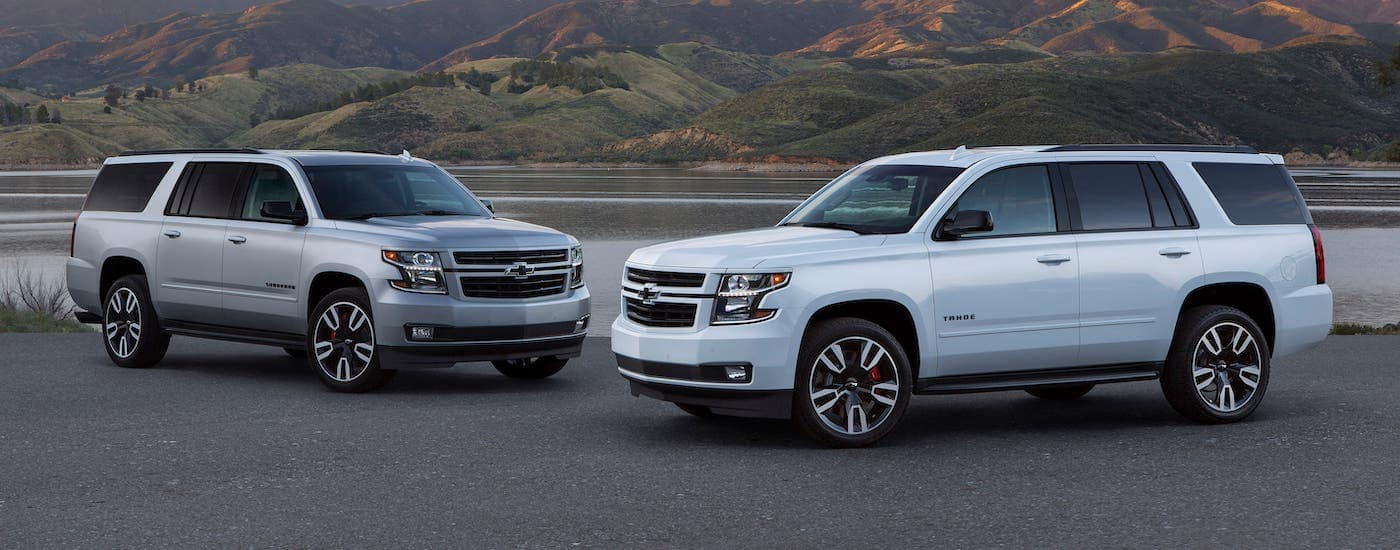 A silver 2019 Chevy Suburban and a white Chevy Tahoe are parked in front of a lake.