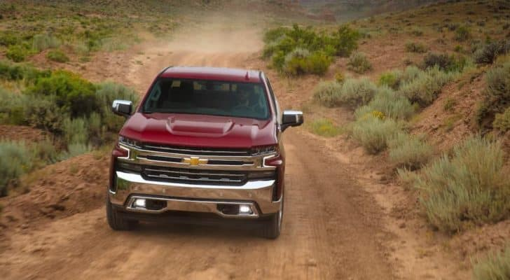 A popular Chevy truck for sale, a red 2020 Chevy Silverado 1500, is shown from the front driving on a dirt road.