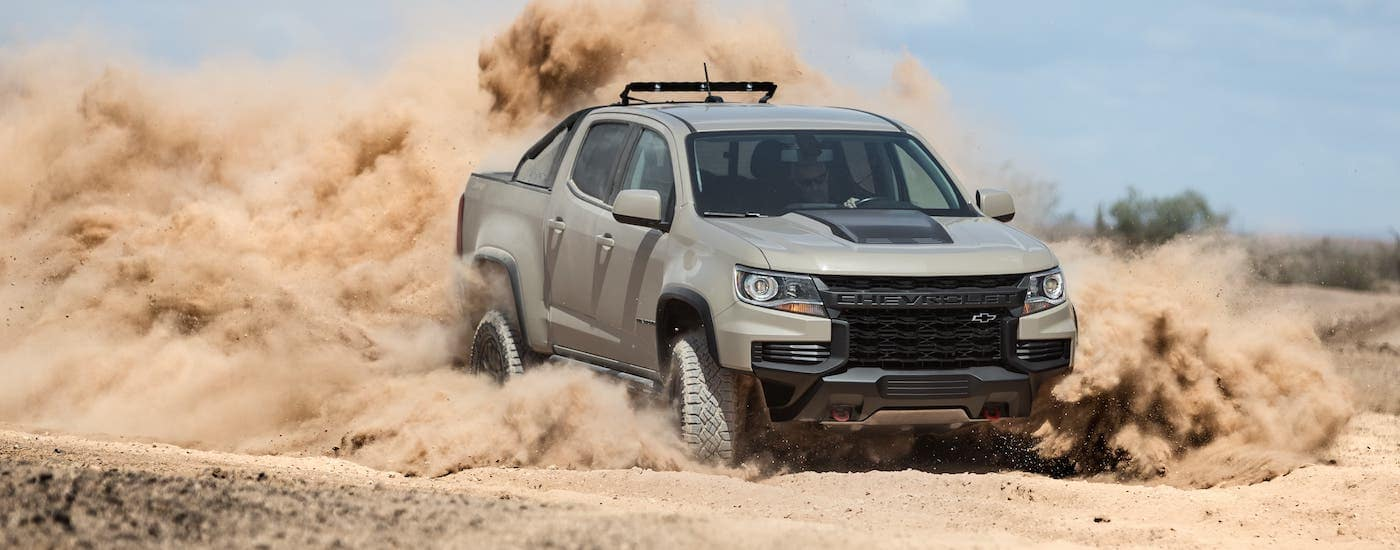 A tan 2021 Chevy Colorado ZR2 is kicking up sand.
