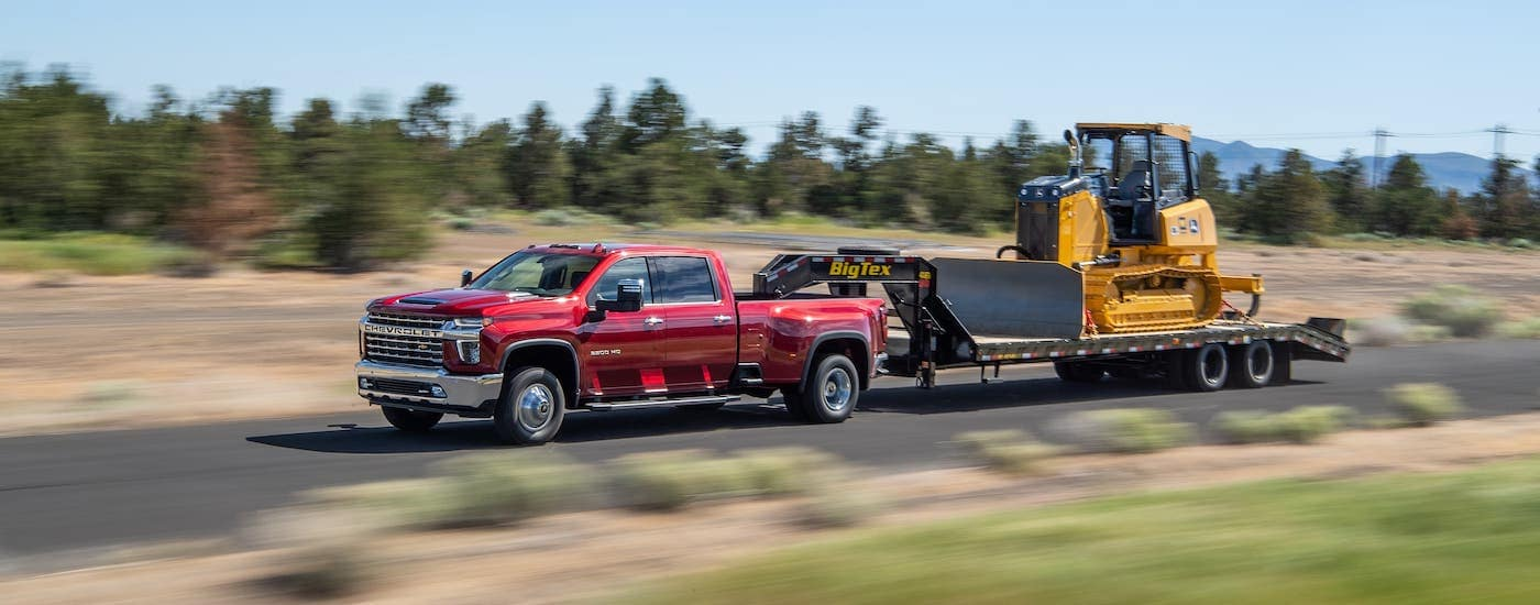 A red 2021 Chevy Silverado 3500HD is towing construction equipment on a highway.
