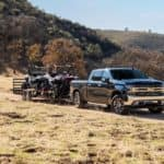 A dark blue 2020 Chevy Silverado is towing side-by-sides on a dirt trail past hills.