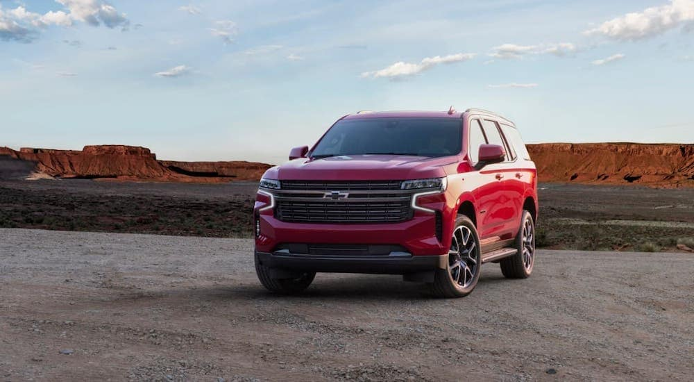 A red 2021 Chevy Tahoe RST, arguably the best SUV, is parked in front of a desert.