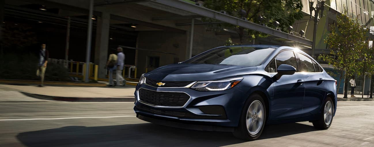 A blue 2017 Chevy Cruze sedan is driving down a highway.