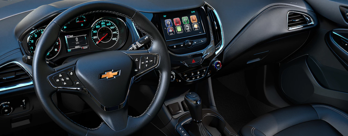 A view of the front interior of a 2018 Cruze with a touchscreen on the dashboard and driver controls and the black steering wheel.