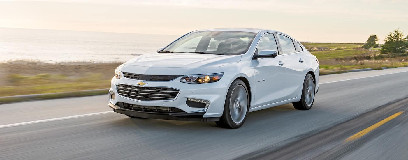 A white 2018 Chevy Malibu is driving down a highway with water in the background.