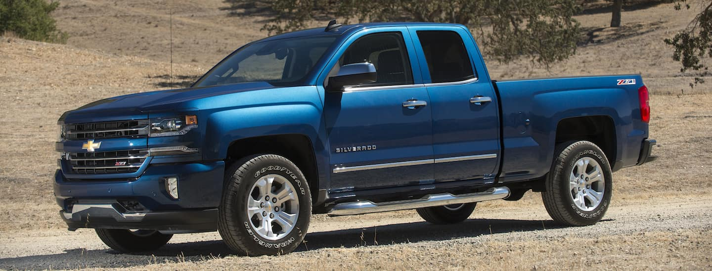 A blue 2018 Silverado is parked on a dirt road with dirt hills in the background.