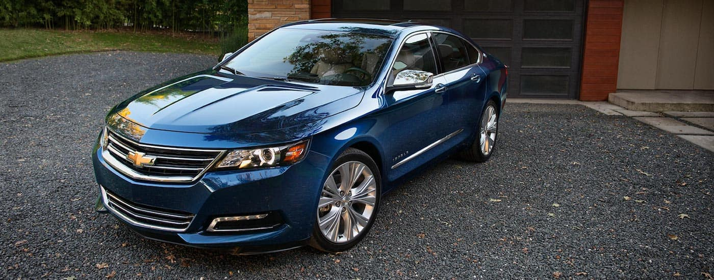 A blue 2018 Impala parked in front of a house garage