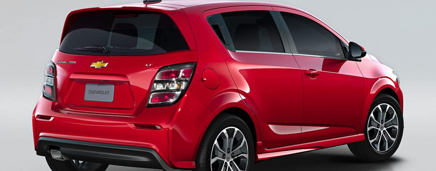 The rear passenger side of a red 2018 Chevy Sonic is parked.