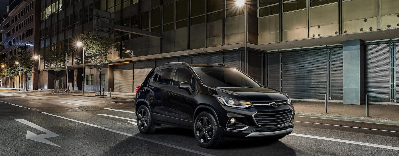 A black 2018 Chevy Trax is parked on a city street at night.