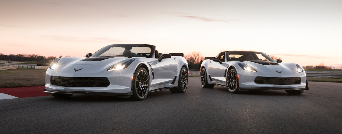 Two white 2018 Chevy Corvettes are parked side-to-side on a race track while the sunsets behind them.