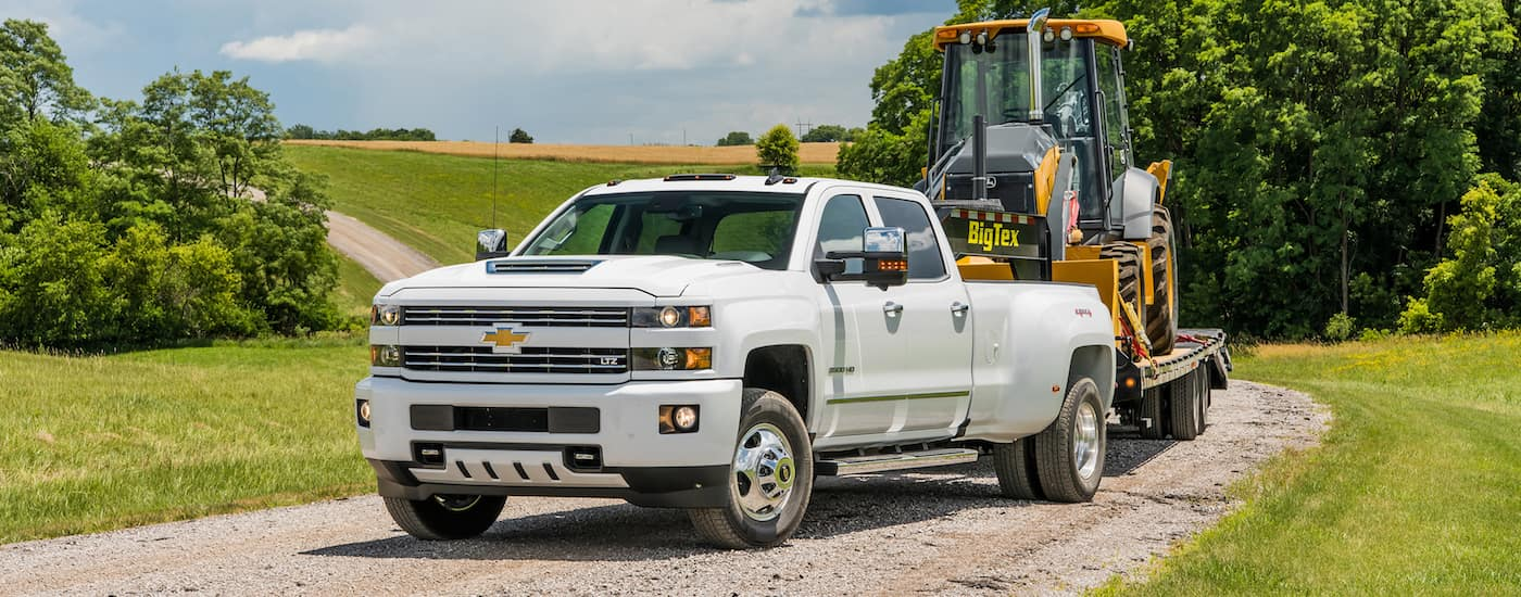 A white 2018 Silverado is parked on a dirt road while towing heavy machinery on a fifth wheel near Cincinnati, OH.