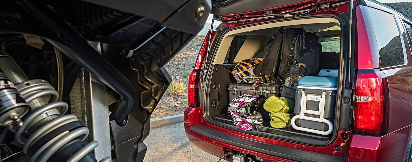 The rear trunk area of the 2018 Chevy Tahoe pile high with sports gear in the desert.