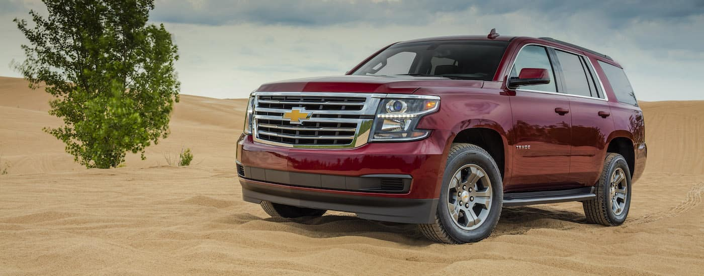 A red 2018 Tahoe is parked in the desert sand on a sunny day.