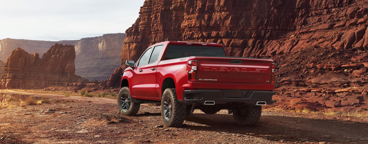 A red 2019 Chevrolet Silverado is parked on a dirt road with midwestern rock mountains in the background.
