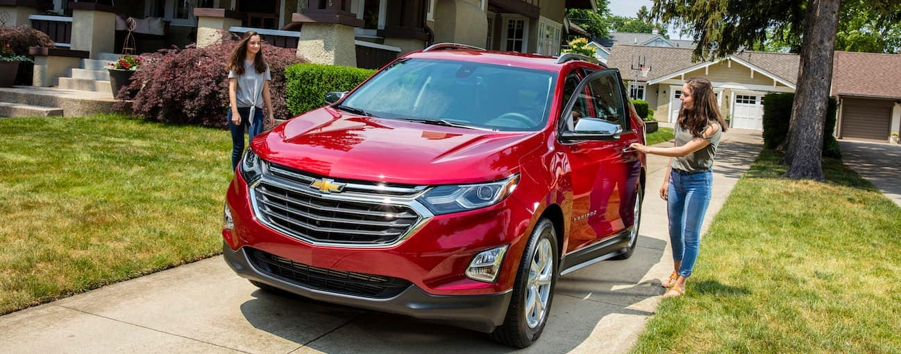 Two teenage females are getting into a 2018 Chevy Equinox on a sunny day.