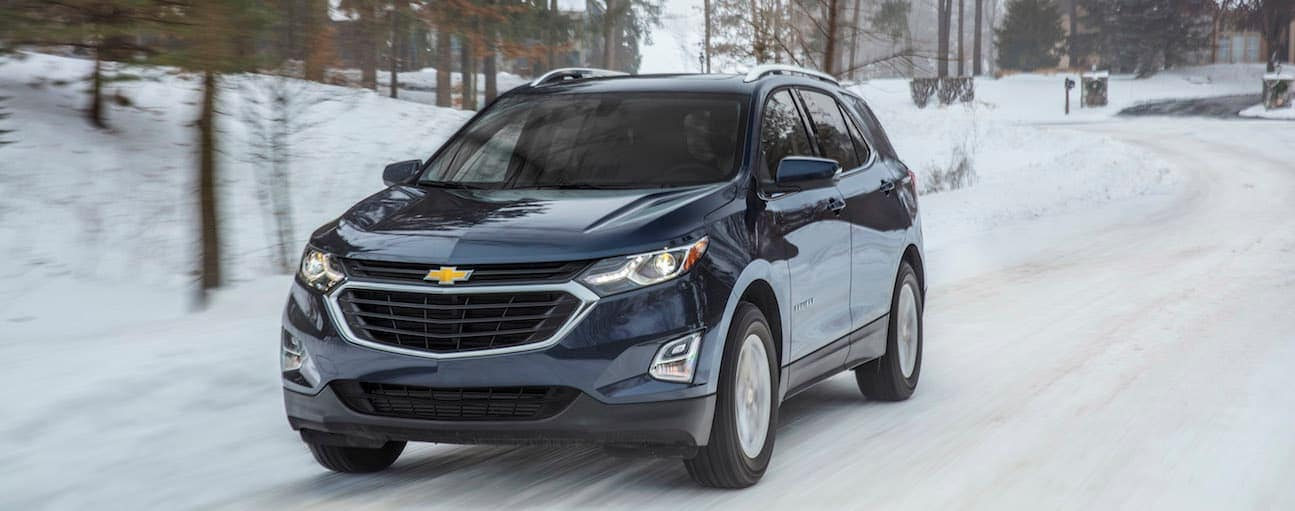 A blue 2018 Chevy Equinox is driving on a snowy road.